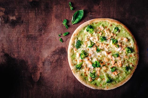 브로콜리, 모짜렐라, 페스토 소스를 곁들인 피자. 나무 배경에 전통적인 이탈리아 구운 피자입니다. 상위 뷰, 복사 공간