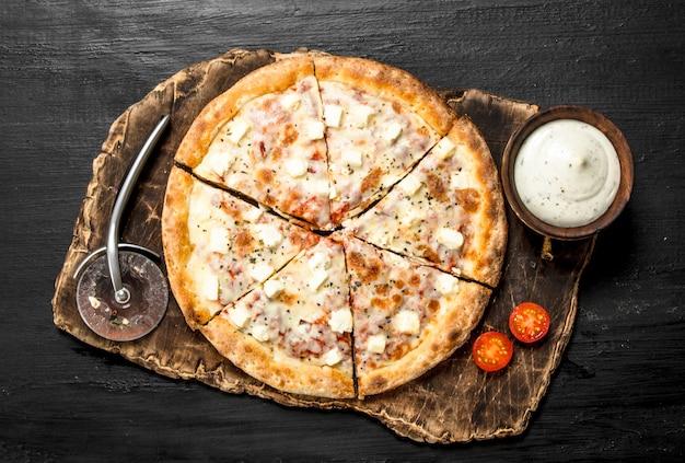 黒い黒板にチーズと香りのよいハーブを添えたピザ。