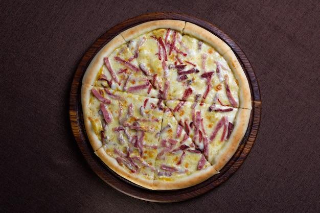 Пицца с сыром и копченой колбасой вид сверху.