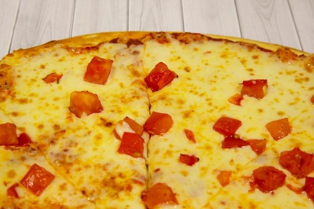 明るい色の木製の背景にチーズとトマト、イタリア料理のピザ