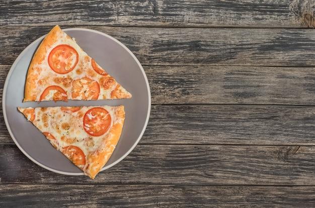 暗い木製の背景にコピースペースとチーズとトマトのピザ。