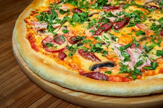 Пицца с сыром, беконом и зеленью на деревянной тарелке. крупный план, выборочный фокус