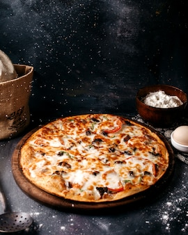 Pizza with cheese on the brown wooden surface on the bright surface