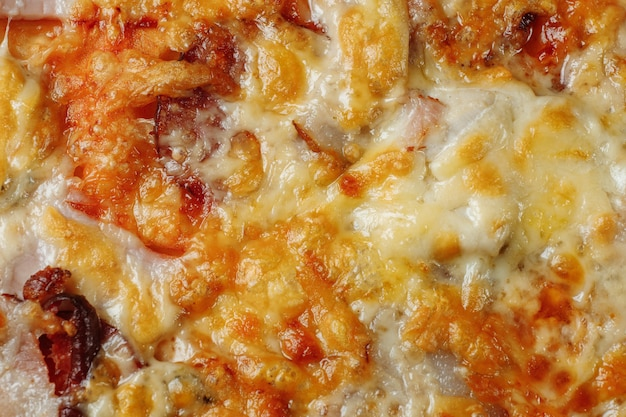 Pizza with cheese, ham and bacon closeup