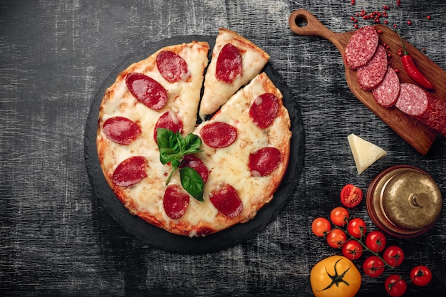 Pizza with cheese and salami on a stone and a black chalk board