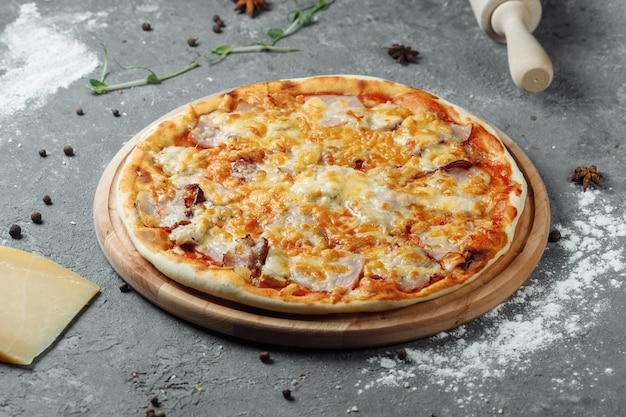 Pizza with cheese, sauce and ham, bacon, salami on gray dark