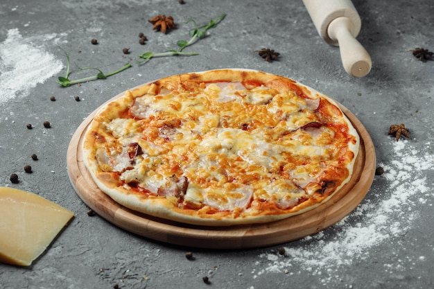 Pizza with cheese, sauce and ham, bacon, salami