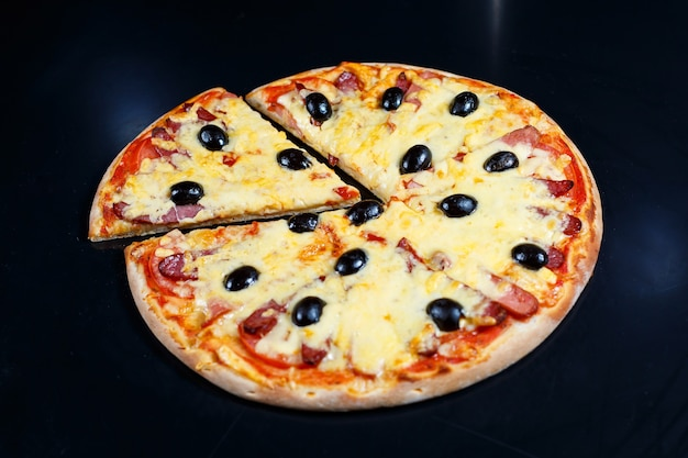 Pizza with cheese tomato sauce, olives, fresh mozzarella, parmesan and basil and meat on a dark background
