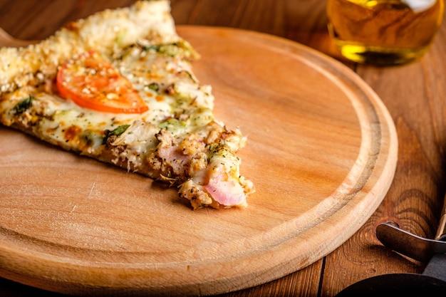 まな板の上のチーズ、トマト、ハム、ゴマのピザ