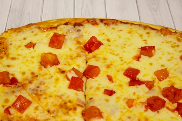 Pizza with cheese and tomatoes, italian cuisine, on a light wooden background