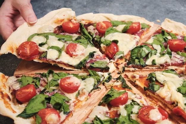 Пицца с сыром, помидорами, шпинатом и копченой колбасой