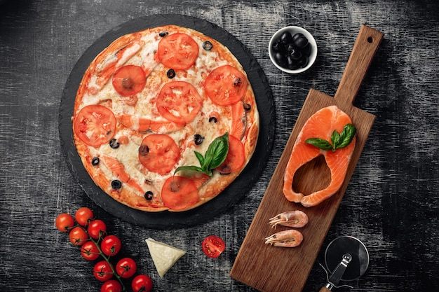 Pizza with cheese, trout, tomatoes, olives and shrimps on chalk board.