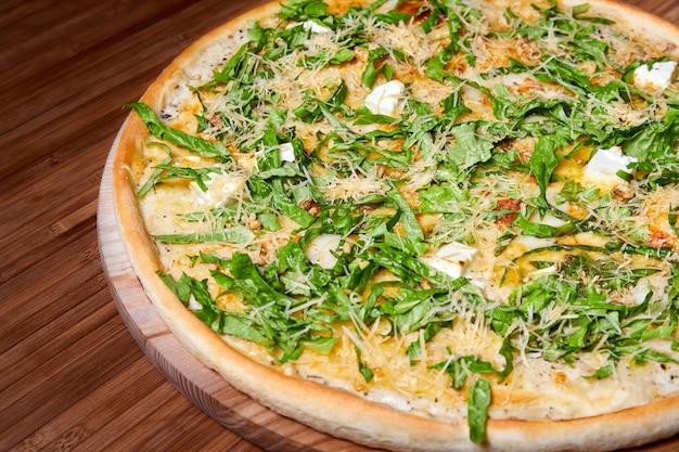 Пицца с сырами и зеленью на деревянной тарелке. крупный план, выборочный фокус
