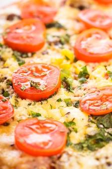 セラミックの白いプレートのクローズアップにチェリートマトとドライバジルのピザ