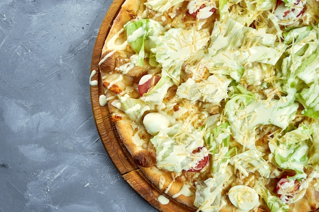 チェリートマト、レタス、パルメザンチーズ、灰色の背景上の鶏のピザ