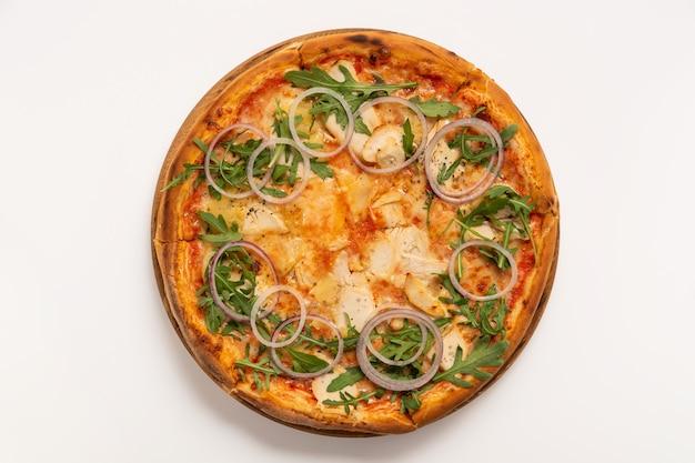 白い表面に分離されたチキンとオニオンリングのピザ。上面図。