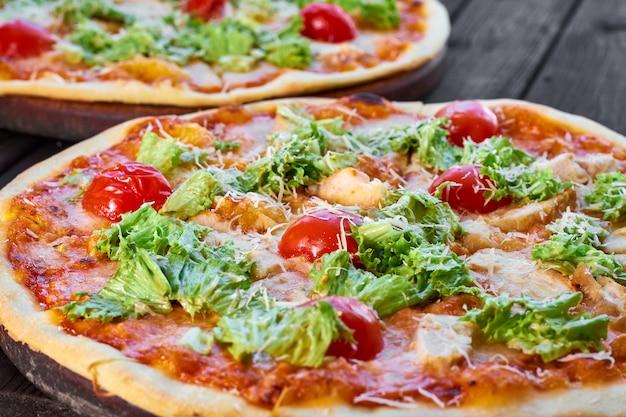 チキン、トマト、木製のテーブルにチーズのピザ