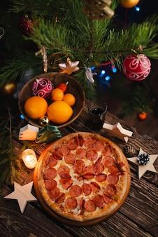 木製のテーブルにクリスマスの装飾が施されたピザ