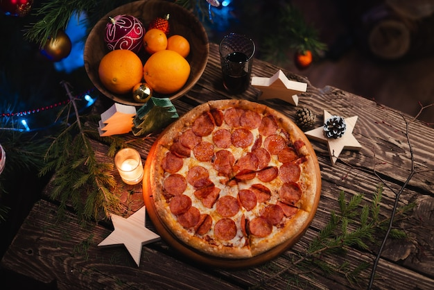 Pizza with christmas decorations on wooden table