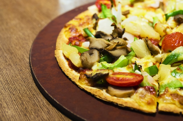 Pizza with colorful vegetable topping ready to be eaten
