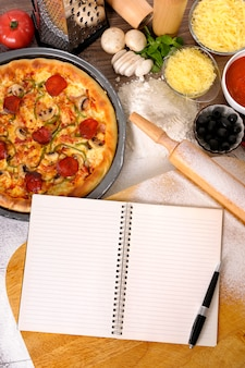 Pizza with cookbook and various ingredients