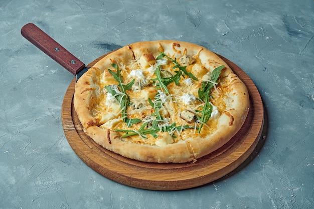 Пицца с четырьмя видами сыра на деревянной доске.