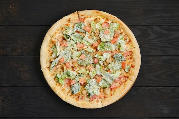 ダークウッドのテーブルにフライドチキンの肉、レタス、トマトのピザ