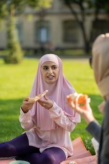 친구와 피자. 친구와 함께 피자를 먹고 분홍색 hijab를 입고 어두운 눈동자 이슬람 여자
