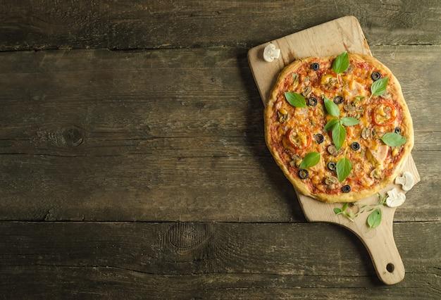 木製の背景にハムとキノコを使ったピザ、食材を厳選して
