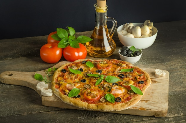 Pizza with ham and mushrooms on wooden surface with selective focus with ingredients