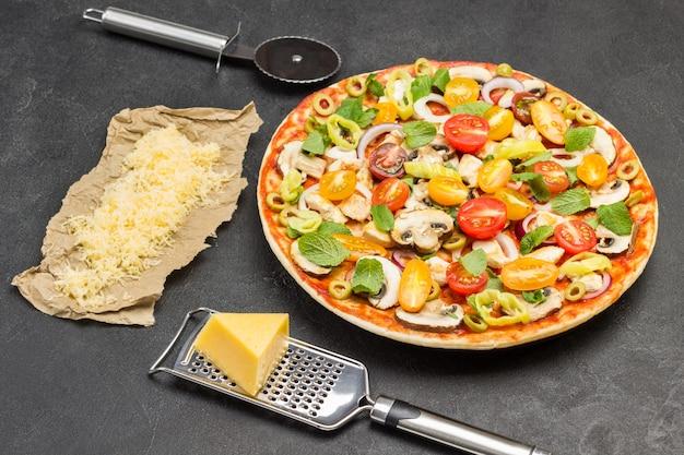 Пицца с ингредиентами готова к выпечке. терка для сыра на столе. бумага, тертый сыр. резак для пиццы. черная поверхность. вид сверху