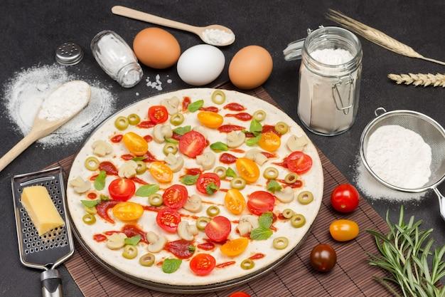 Пицца с ингредиентами готова к выпечке