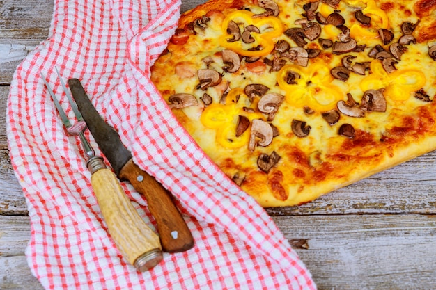 Pizza with a knife and a towel on wooden background.