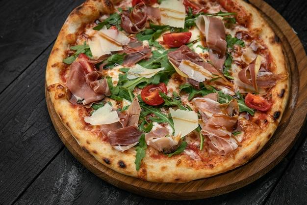 어두운 탁자에 있는 나무 판자에 고기 파마산 치즈와 토마토를 넣은 피자