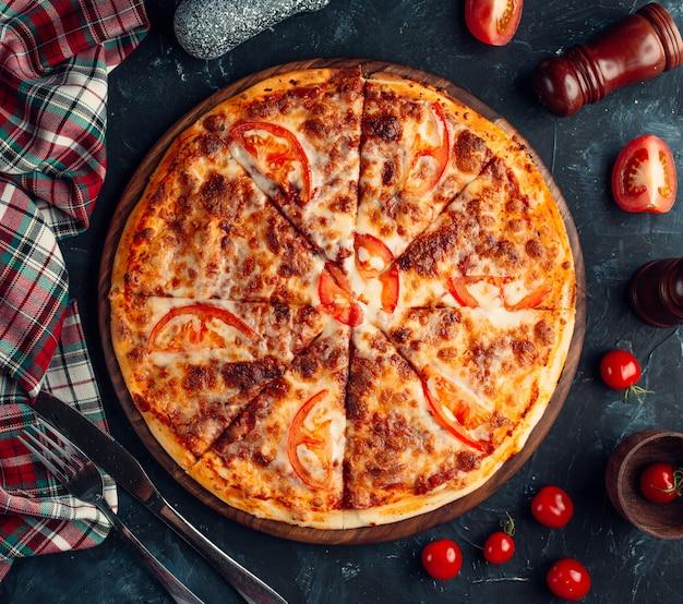 Пицца с мясной начинкой и кусочками помидоров.