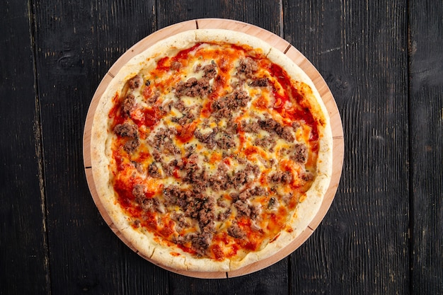 Pizza with minced meat and tomato sauce on the dark wooden table