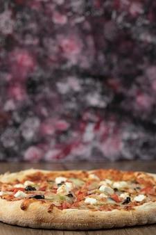 Pizza con ingredienti misti e formaggio bianco tritato.