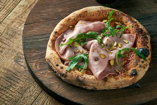 木の板にモルタデッラ、ルッコラ、ピスタチオを添えたピザ。イタリア料理