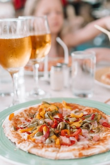 Pizza with mozzarella cheese, olive, fresh tomato and pesto sauce. served at restaurant table