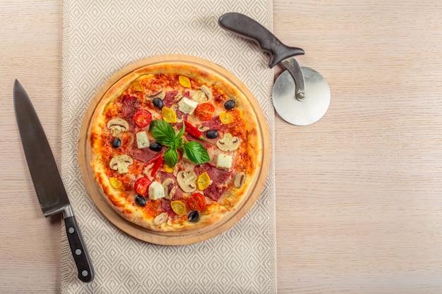 Pizza with mozzarella, ham, cherry tomatoes, black olives