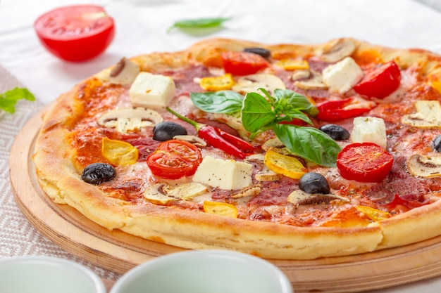 Pizza with mozzarella, ham, cherry tomatoes, black olives