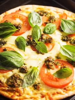 Пицца с моцареллой, помидорами и песто из зеленого базилика, вид крупным планом