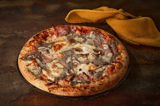 Pizza with mushroom sauce, ham, mushrooms, tomato paste.