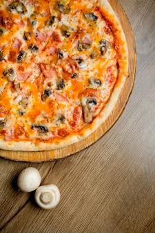 キノコ、ハム、ハーブのピザ