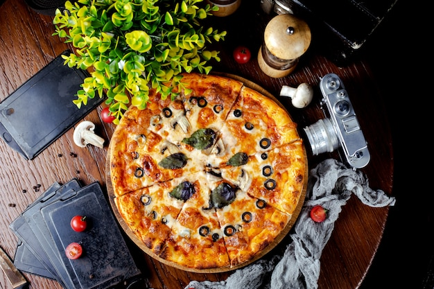 Pizza with mushrooms, olives and basil leaves