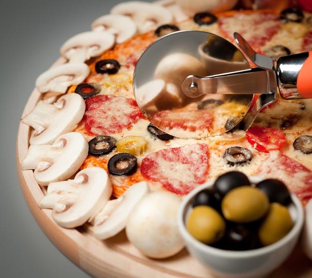 버섯, 소시지, 올리브를 곁들인 피자 컷 원형 칼