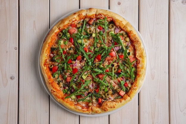 Pizza with mushrooms, zucchini, bell pepper, onion and arugula