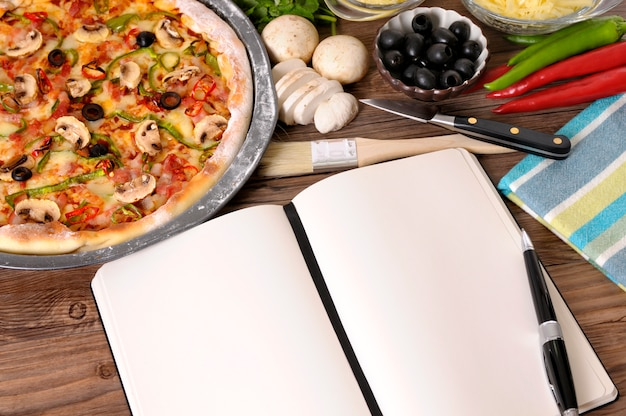Pizza with notebook or cookbook and ingredients