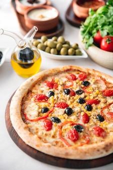 Pizza with olives bell peppers tomatoes and corn