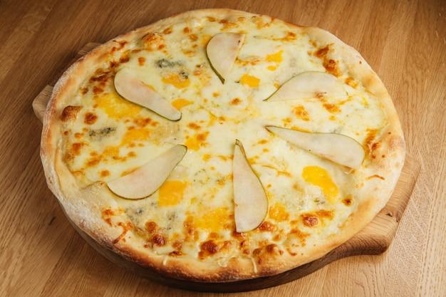 木の板に洋ナシとゴルゴンゾーラチーズのピザ